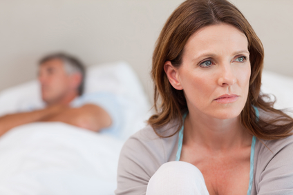 Sad woman on bed with her husband in the background